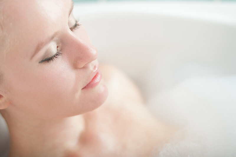 beautiful woman relaxing in bath with foam in bathroom